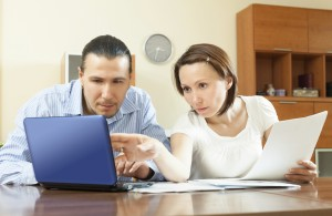 couple looking  documents in laptop